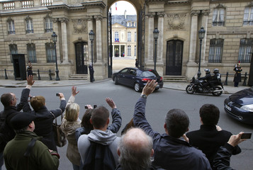 The motorcade with France's President Sarkozy and his wife Carla Bruni-Sarkozy arrives at the Elysee Palace in Paris after they voted in the second round of the 2012 presidential elections