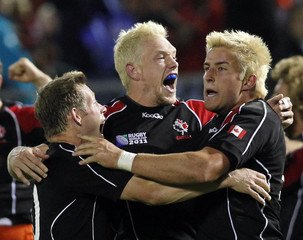 Canada's Ander Monro, Phil Mackenzie and Dth Van Der Merwe celebrate after winning their Rugby World Cup Pool A match against Tonga at Northland Events Centre in Whangarei