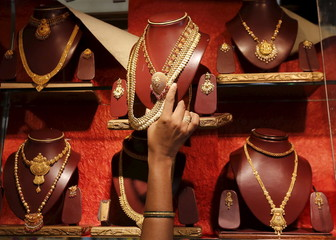 A saleswoman keeps a gold necklace in a shelve at a showroom in Mumbai