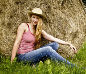 Portrait of young and attractive woman in hat posing on the stack of hay in the field on sunny day.