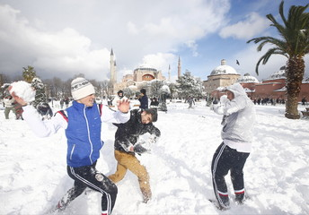 Boys play in the snow at Sultanahmet square, with the Byzantine era monument of Hagia Sophia in the background in Istanbul