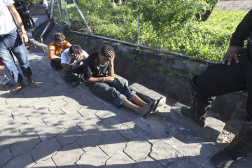 People sit on the ground after they were detained by the police during clashes between supporters of the FSLN and the Alliance PLI in La Paz Centro town