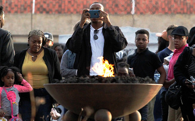 A man takes a picture of the eternal flame as visitors tour the grounds around The King Center on the Martin Luther King, Jr. holiday in Atlanta