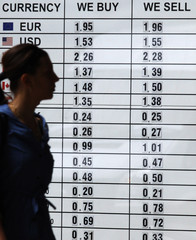 A pedestrian walks past a currency exchange board in central Sofia