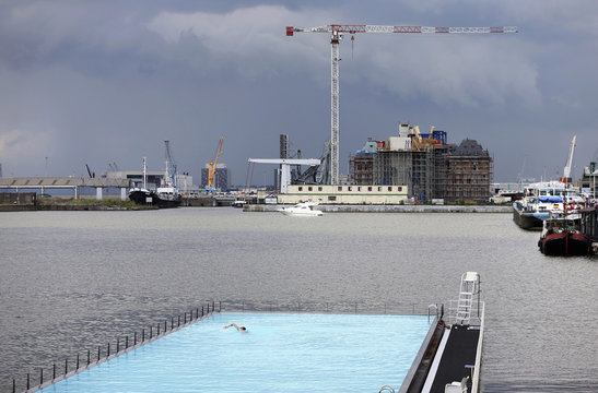 "A man enjoys a floating open-air swimming pool called ""badboot"" in the port of Antwerp"