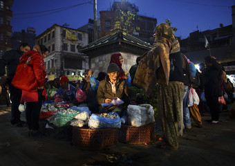 A street vendor sells mushrooms to a customer at Ashon, one of the busiest market places, in central Kathmandu