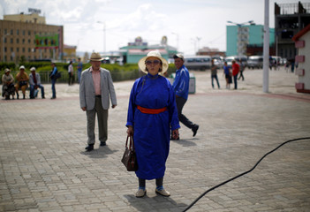 A woman stands as she watches a rally of N. Udval, Mongolian People's Revolutionary Party's (MPRP) candidate for Mongolian President, during a campaign in Baganuur
