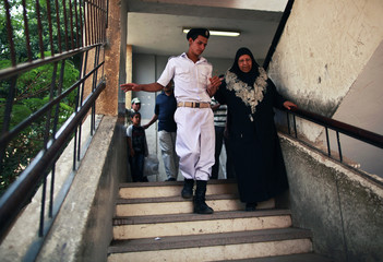 An Egyptian policeman helps a woman after casting her vote at a polling station in Cairo
