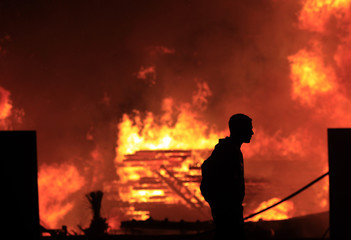 A protester walks in front of a fire in downtown Cairo