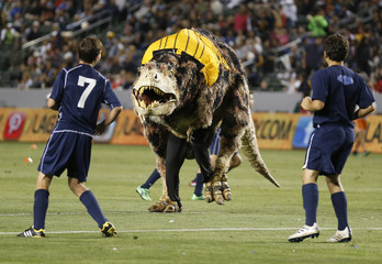A person in a Tyrannosaurus Rex dinosaur costume runs on the field as young boys play an exhibition soccer match during halftime of the MLS soccer game between the Los Angeles Galaxy and Seattle Sounders FC in Carson