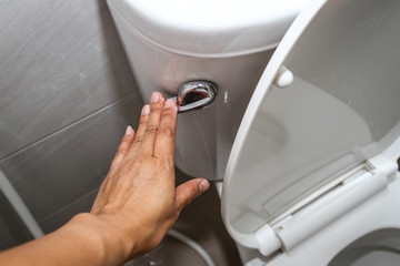 A woman hand pressing a white toilet bowl or flush toilet in the bathroom.