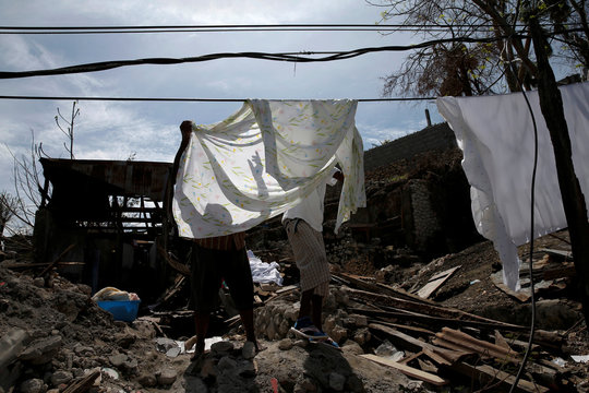 People hang sheets on power lines in front of their destroyed house after Hurricane Matthew hit Jeremie