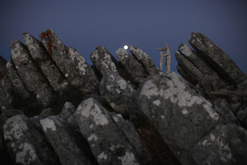 A view of a monument dedicated to forest rangers as the supermoon sets over the horizon at dawn at a nature park and biosphere reserve near Malaga