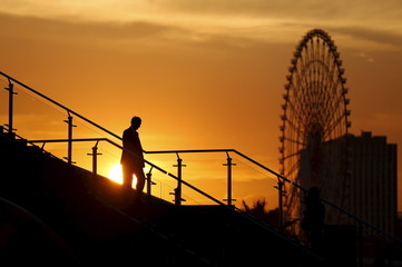 A man walks on a bridge as a big ferris wheel is seen in the background, during sunset in Tokyo