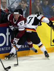 Germany's Ullmann fights for the puck with Latvia's Meija during their 2013 IIHF Ice Hockey World Championship preliminary round match at the Hartwall Arena in Helsinki