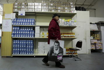 "A volunteer walks past foods holding a picture of late French comic Coluche in a charity food distribution centre ""Les Restos Du Coeur"" (Restaurants of the Heart) in Nice"