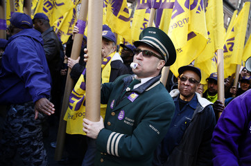 Doorman Joe Soto marches in his uniform with thousands of members of the Service Employees International Union (SEIU) during a protest in support of a new contract for apartment building workers in New York City