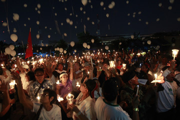 Pro-government supporters hold candles and release balloons during an election campaign in Nonthaburi province