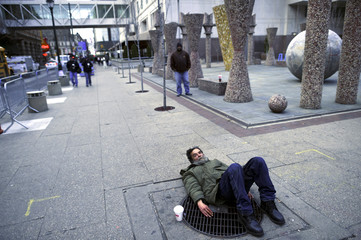 "A homeless man lies on a steam vent outside the location of the 2017 ""Congress of Tomorrow"" Joint Republican Issues Conference in Philadelphia, Pennsylvania, U.S."