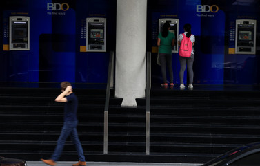 A woman withdraw cash money at the Automated Teller Machine (ATM) of the Banco de Oro (BDO) Unibank, Inc building in Makati city, metro Manila, Philippines