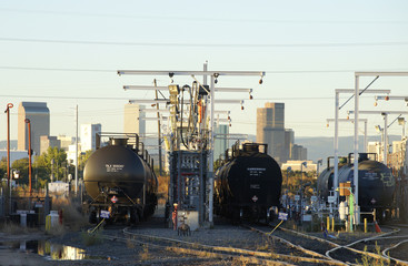 Oil tanker railcars are parked at a filling rack at sunrise with the Denver downtown skyline in the background