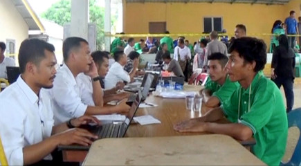 Still image from video shows police and immigration officials taking data from survivors after a speedboat carrying Indonesian migrant workers crashed and sank off the island of Batam