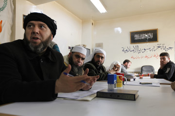 "Suleiman, leader of an Islamist rebel group in Aleppo called ""The Authority for the Promotion of Virtue and Supporting the Oppressed"", sits with Sheikhs from the group in Aleppo"