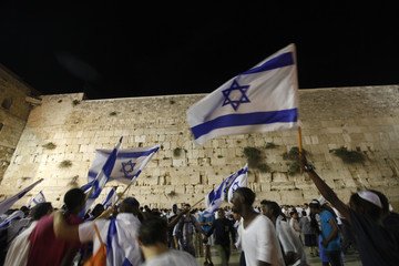 Israeli youths dance with national flags in front of the Western Wall during a parade marking Jerusalem Day in Jerusalem