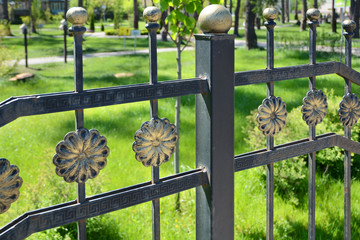 Beautiful wrought fence. Image of a decorative cast iron fence. metal fence close up. Metal Forged Fence. Beautiful fences with artistic forging