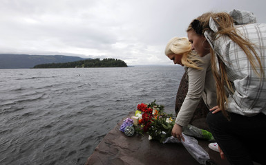 People place flowers in front of Utoeya island northwest of Oslo