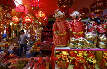 A vendor walks along Chinese Lunar New Year decoration shops in central Phnom Penh