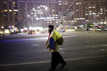 A priest carries a selfmade crucifix during a demonstration in Bucharest