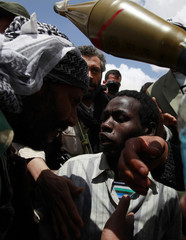 Rebel fighters question a man from Chad at a checkpoint after he was captured in Ajdabiyah
