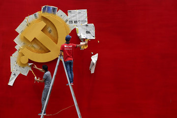 Workers peel papers off a wall as they re-paint the Chinese Communist Party flag on it at the Nanhu revolution memorial museum in Jiaxing
