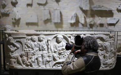 A photographer takes pictures of a marble low-relief decorating a sarcophagus inside the catacomb of Priscilla in Rome