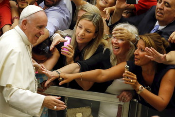 Faithful react as Pope Francis arrives to lead his weekly audience in Paul VI hall at the Vatican City