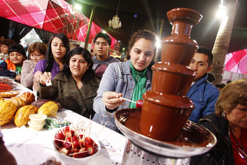 A girl dips a strawberry into a chocolate fountain as fellow visitors line up during the Gastronomic Fair 'Mistura' 2010 in Lima