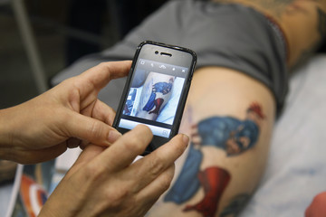 Artist Sean Karn takes a picture of his work, a tattoo of Captain America, to show his client Ron Raucci during the Hampton Roads Tattoo Festival in Virginia