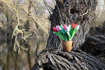 Handmade tulips flowers from fabric in ceramic cup on tree in forest. Creativity, ideas