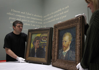 Gallery staff pose for photographers with self-portraits by artists Gaugin and Van Gogh at the Lady Lever Art Gallery in Port Sunlight, northern England