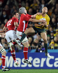 Australia Wallabies' Quade Cooper and Wales' Jonathan Davies fight for a high ball during their Rugby World Cup third place play-off match at Eden Park in Auckland