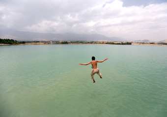 An Afghan boy jumps for a swim at Qargha lake in Kabul