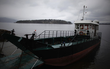 A ship is anchored on a small quay on the shore of Tyrifjorden lake in front of Utoeya island
