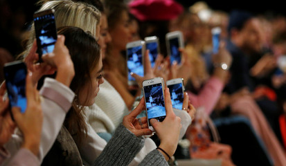 A so-called media influencer takes pictures as a model presents a creation by Marina Hoermanseder on the sidelines of the Berlin Fashion Week Autumn/Winter 2017/2018 in Berlin