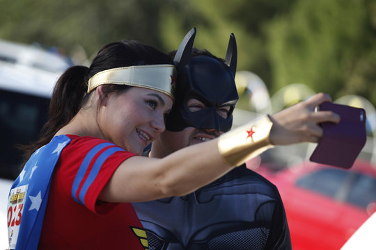 """Participants dressed as Wonder Woman and Batman take a selfie during the """"Superheroes Corriendo Por Peque-os Inocentes"""" (Superheroes Running For Little Innocents) race at Chamizal park in Ciudad Juarez"""