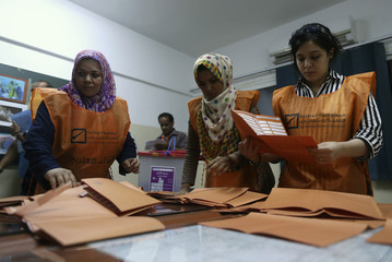 Electoral workers count ballots after a polling station closed in Benghazi