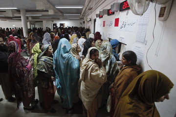 Woman stand in queue to receive free medication from a pharmacy at the Punjab Institute of Cardiology (PIC) in Lahore