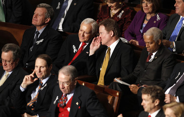 Members of the Republican and Democratic parties sit with each other during the State of the Union address in Washington