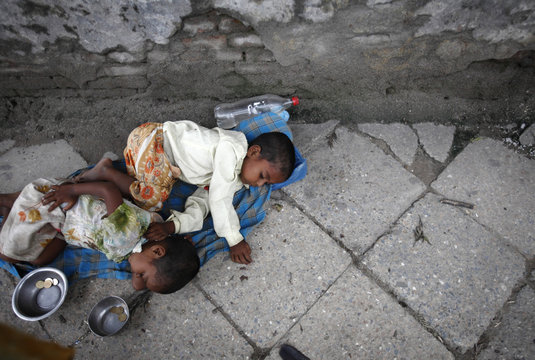 Children fall asleep along the side of the road while begging for money in Kathmandu