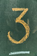 Number three written hand chalk on board.Text number three on chalkboard